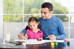 Little Girl And Father Drawing Pictures Together. Little Girl And Father Are Drawing Pictures Together stock photography