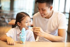 Little girl with father eating ice cream stock images