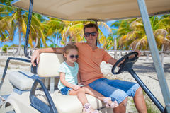 Little girl with father golf cart on tropical Royalty Free Stock Image