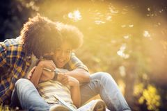 Little girl in father hug. African American father and daughter playing in park. Little girl with book stock photography