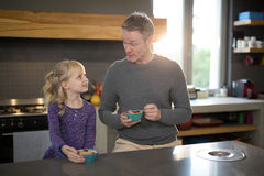 Little girl and father looking at each other while eating fruits from a bowl Stock Image