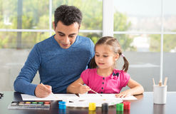 Little Girl And Father Painting Pictures Together. Little Girl And Father Are Painting Pictures Together royalty free stock photography