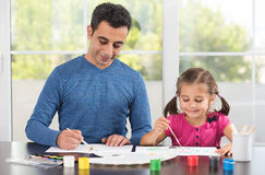 Little Girl And Father Painting Pictures Together. Little Girl And Father Are Painting Pictures Together Royalty Free Stock Photos