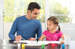 Little Girl And Father Painting Pictures Together. Little Girl And Father Are Painting Pictures Together Stock Image