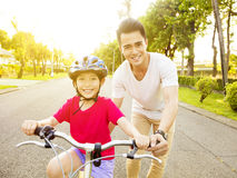 little girl with father practice to riding  bicycle Royalty Free Stock Photography