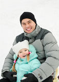 Little girl with father riding a sledge on winter day Royalty Free Stock Images