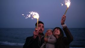 Little girl on father`s arms watching her mother, father waving sparklers on the beach in the evening dusk. Happy young. Family stock footage