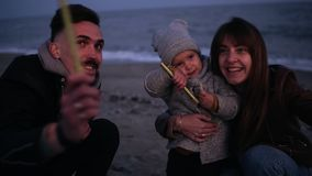 Little girl on father`s arms watching her mother, father waving sparklers on the beach in the evening dusk. Happy young. Family, Happy face, seaside. Slow stock video footage