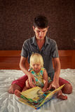 Little girl and father sit on sofa and look into book Royalty Free Stock Photos