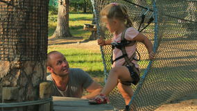 Little girl with father spends leisure time in rope park stock video
