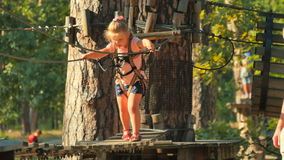 Little girl with father spends their leisure time in rope park stock video