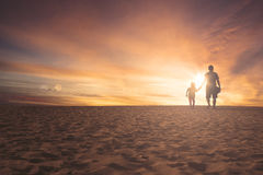 Little girl and father walking on sand. Rear view of little girl and father walking together on the sand dune at sunset time stock photos