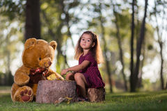 Little girl feed your teddy bear Royalty Free Stock Photo