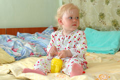 Little girl with feeding bottle sit on the bed. Stock Photo