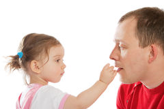 Little girl feeding dad Royalty Free Stock Photography