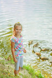 Little girl feeding ducks. Little beautiful girl feeding ducks at pond in summer city park stock photography