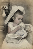 Little girl is feeding her doll Royalty Free Stock Photography