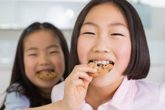 Little girl feeding her elder sister a cookies in kitchen Royalty Free Stock Photo