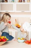 Little girl feeding her sister tomato while Royalty Free Stock Photography