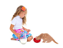 Little girl feeding kitten with milk Stock Photos