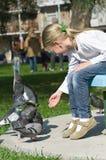 Little girl feeding Pigeons Stock Photo
