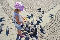 Little girl feeding pigeons. On the square Stock Photos