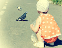 Little girl feeding pigeons. Royalty Free Stock Photography