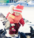 Little girl feeding pigeons with hands Stock Photo