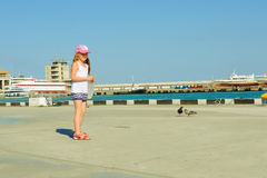 Little girl feeding pigeons on waterfront Royalty Free Stock Images