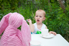 Little Girl feeding Pink Bunny Rabbit Stock Photography