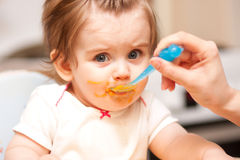 Little girl feeding from a spoon on blue chair. Royalty Free Stock Photo