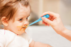 Little girl feeding from a spoon on blue chair. Royalty Free Stock Photography