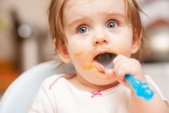 Little girl feeding from a spoon on blue chair. Royalty Free Stock Image