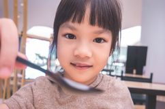 Little girl feeding you with a spoon stock photo