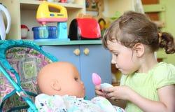 Little girl feeds doll stock photos
