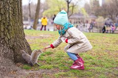 Little girl feeds a squirrel in Central park, New Royalty Free Stock Photos