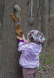 Little girl feeds a squirrel. Royalty Free Stock Photography