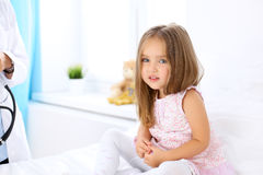 Little girl is feeling pain while doctor examine her in hospital Royalty Free Stock Photos