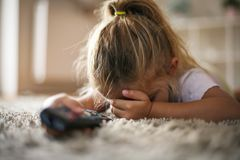 Little girl feeling scared while watching TV. royalty free stock photos