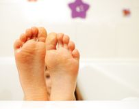 Little girl feet covered with water in the bathtub Royalty Free Stock Images