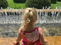 Little girl with feet in a fountain on hot day stock photography