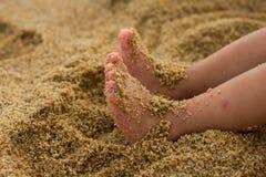 Little girl feet on the sandy beach Stock Photos