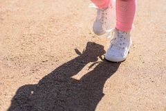 Little girl feet only with white lace high tops gym shoe. Low angle ground level view of little child& x27;s white shoes standing outside on trail in sunlight royalty free stock photography
