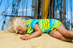 Little girl fell asleep on the deck of a sailboat Stock Image