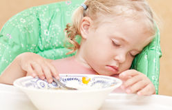 Little girl fell asleep at the table eating soup. With a spoon in her hand stock photos