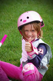 Little girl in pink fell off bike but thumbs up all is okay. Stock Photos