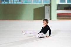 Little girl fell  training in rhythmic athletics Stock Image
