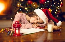 Little girl felt asleep while writing to Santa Stock Image