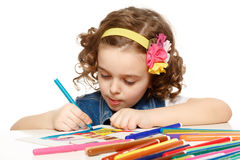 Little girl with felt-tip pen drawing in kindergarten. White background. Isolated stock image