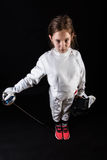 Little girl in fencing costume relaxing after fight. Smiling little girl in fencing costume without mask relaxing after fight royalty free stock photos
